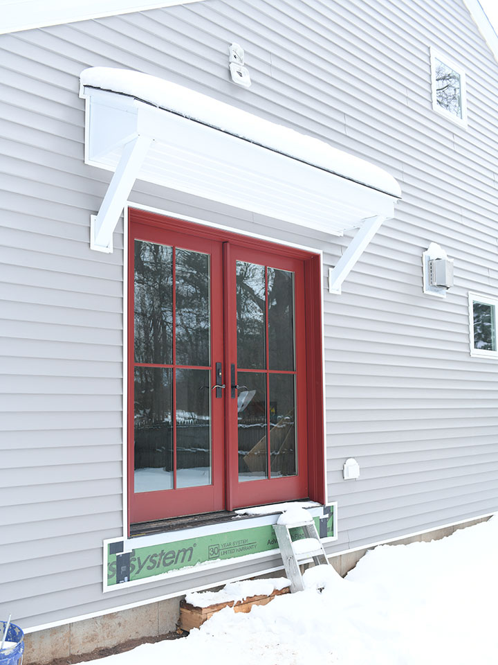Exterior door replaced with red Marvin French doors on house with gray siding